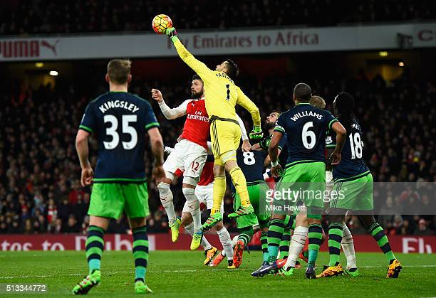 Lukasz Fabianski of Swansea City punches clear from Olivier Giroud of Arsenal during the Barclays Premier League match between Arsenal and Swansea...