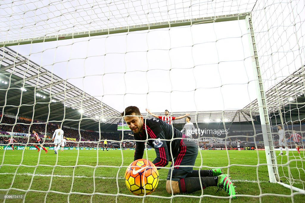 Lukasz Fabianski of Swansea City watches the ball at the back of the net after Shane Long (2nd L) of Southampton scores his team's first goal during the Barclays Premier League match between Swansea City and Southampton at Liberty Stadium on February 13, 2016 in Swansea, Wales.