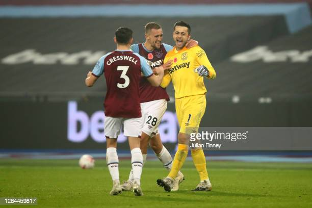Lukasz Fabianski of West Ham United celebrates with teammates Aaron Cresswell and Tomas Soucek after saving a penalty from Ademola Lookman of Fulham...