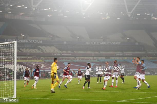 Lukasz Fabianski of West Ham United is embraced by teammates after he saves a penalty from Ademola Lookman of Fulham during the Premier League match...