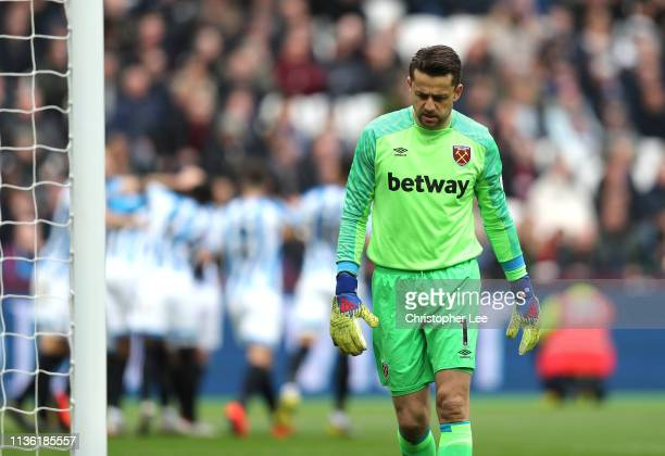 Lukasz Fabianski of West Ham United reacts after Juninho Bacuna of Huddersfield Town scores his team's first goal during the Premier League match...