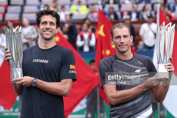 Lukasz Kubot of Poland and Marcelo Melo of Brazil celebrate with trophy during the Award Ceremony after winning the Men's doubles final match against...