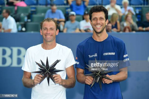 Lukasz Kubot of Poland and Marcelo Melo of Brazil pose with their trophies after defeating Nicholas Monroe and Tennys Sandgren in the men's doubles...
