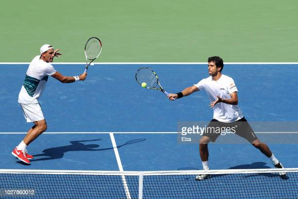 Lukasz Kubot of Poland and Marcelo Melo of Brazil return the ball during their men's doubles semifinal match against Malek Jaziri of Tunisia and Radu...