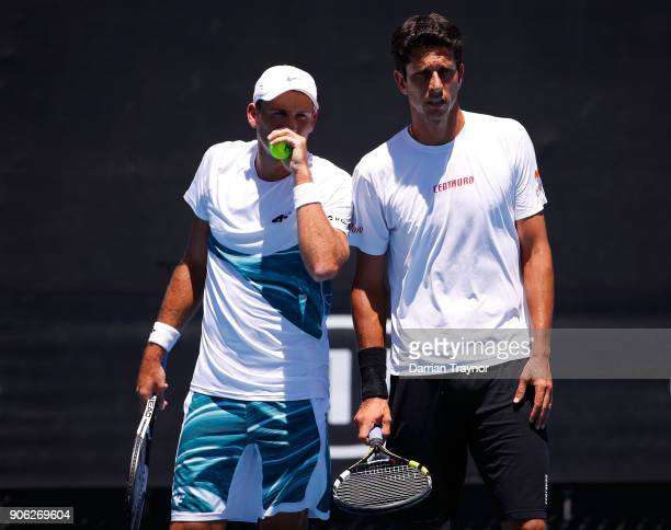 Lukasz Kubot of Poland and Marcelo Melo of Brazil talk tactics in their first round men's doubles match against Paolo Lorenzi of Italy and Mischa...