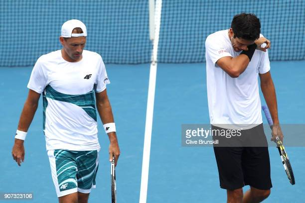 Lukasz Kubot of Poland and Marcelo Melo of Brazil talk tactics in their second round men's doubles match against Luke Saville of Australia and Max...
