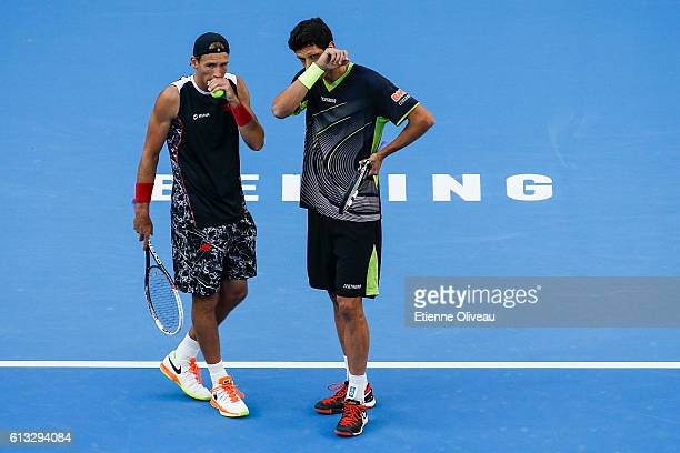 Lukasz Kubot of Poland and Marcelo Melo of Brazil talk tactics against Jack Sock of the United States and Bernard Tomic of Australia during the Men's...
