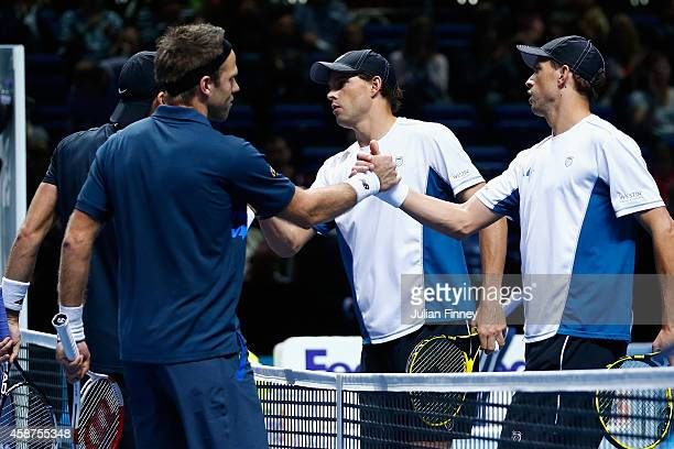 Lukasz Kubot of Poland and Robert Lindstedt of Sweden are congratulated by Bob and Mike Bryan of USA in the round robin doubles during day two of the...