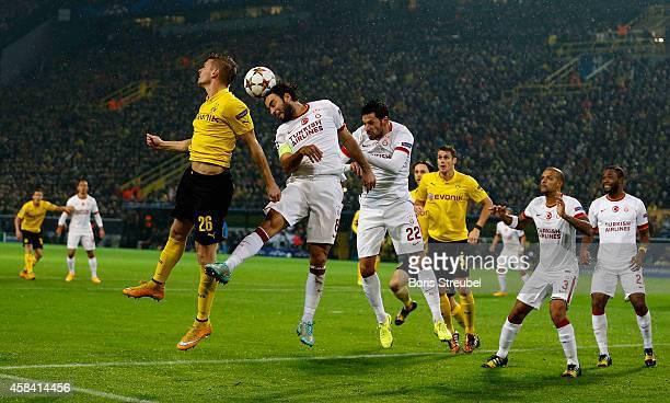 Lukasz Piszczek and Sebastian Kehl of Borussia Dortmund jump for a header with Selcuk Inan and Hakan Balta of Galatasaray during the UEFA Champions...