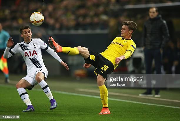 Lukasz Piszczek of Borussia Dortmund beats Tom Carroll of Tottenham Hotspur to the ball during the UEFA Europa League Round of 16 first leg match...