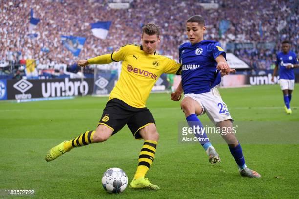 Lukasz Piszczek of Borussia Dortmund is challenged by Amine Harit of FC Schalke 04 during the Bundesliga match between FC Schalke 04 and Borussia...