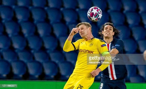 Lukasz Piszczek of Borussia Dortmund jumps for a header with Edinson Cavani of Paris SaintGermain during the UEFA Champions League round of 16 second...