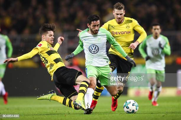Lukasz Piszczek of Borussia Dortmund , Yunus Malli of VfL Wolfsburg and Julian Weigl of Borussia Dortmund battle for the ball during the Bundesliga...