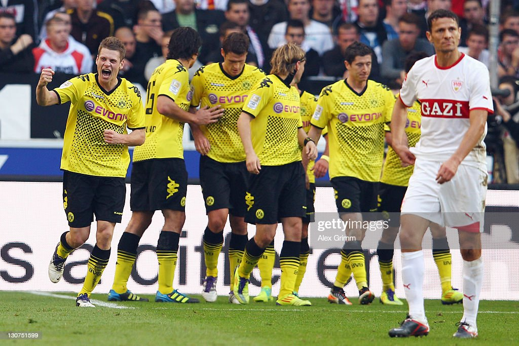Lukasz Piszczek (L) of Dortmund celebrates his team's first goal with team mates as Khalid Boulahrouz of Stuttgart (R) reacts during the Bundesliga match between VfB Stuttgart and Borussia Dortmund at Mercedes-Benz Arena on October 29, 2011 in Stuttgart, Germany.