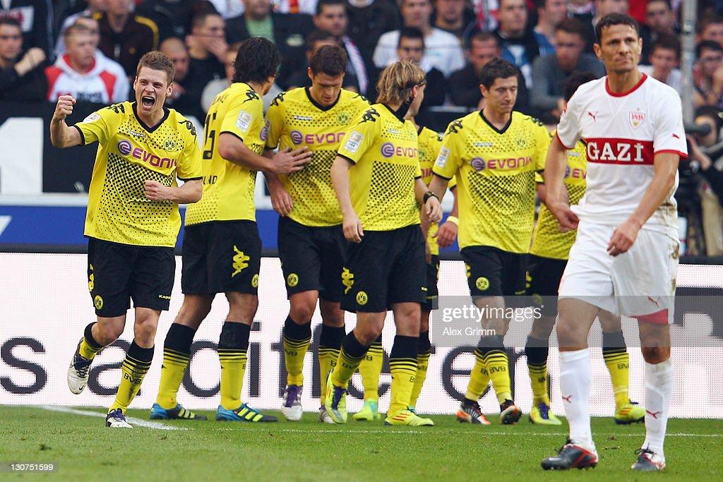 Lukasz Piszczek (L) of Dortmund celebrates his team's first goal with team mates as Khalid Boulahrouz of Stuttgart (R) reacts during the Bundesliga match between VfB Stuttgart and Borussia Dortmund at Mercedes-Benz Arena on October 29, 2011 in Stuttgart, Germany.