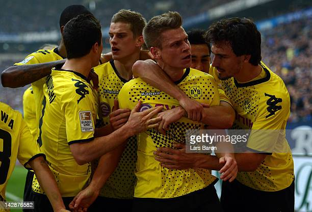 Lukasz Piszczek of Dortmund celebrates with team mates after scoring his teams first goal during the Bundesliga match between FC Schalke 04 and...