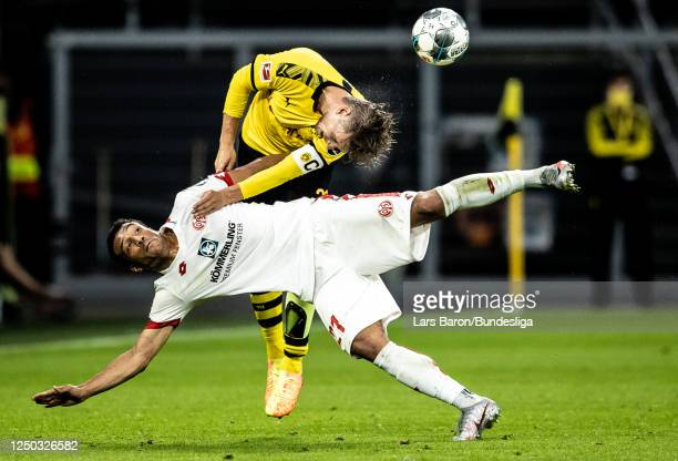 Lukasz Piszczek of Dortmund challenges Karim Onisiwo of Mainz during the Bundesliga match between Borussia Dortmund and 1 FSV Mainz 05 at Signal...