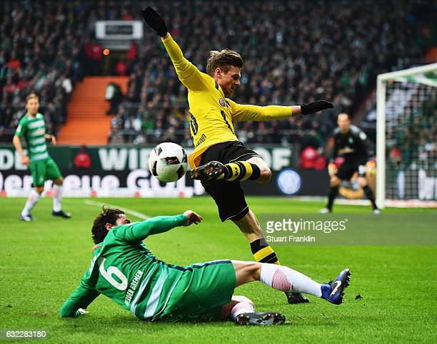 Lukasz Piszczek of Dortmund is challenged by Thomas Delaney of Bremen during the Bundesliga match between Werder Bremen and Borussia Dortmund at...