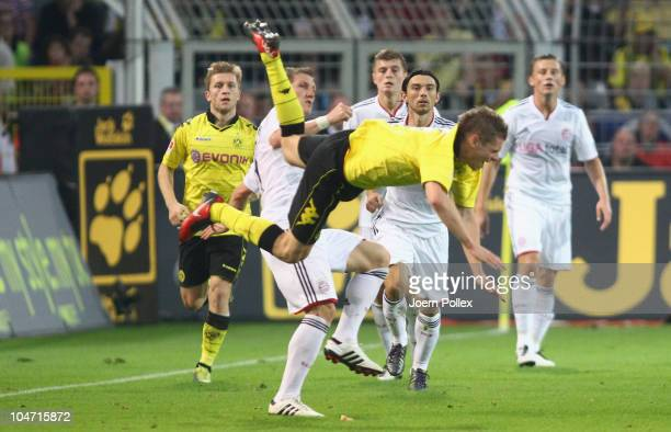 Lukasz Piszczek of Dortmund is tackled by Bastian Schweinsteiger during the Bundesliga match between Borussia Dortmund and FC Bayern Muenchen at...