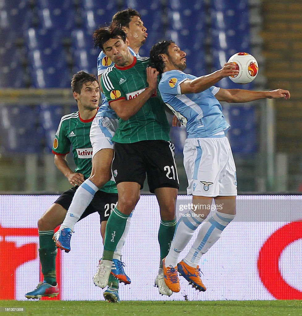 Lukasz Rzezniczak (L) and his teammate Ivica Vrdoljak of Legia Warszawa fight with Hernanes and Sergio Floccari of SS Lazio during the Uefa Europa League Group J match between SS Lazio and Legia Warszawa at Stadio Olimpico on September 19, 2013 in Rome, Italy.