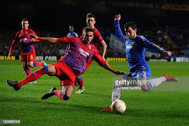 Lukasz Szukala of FC Steaua Bucuresti goes into block Eden Hazard of Chelsea's cross during the UEFA Europa League Round of 16 Second leg match...