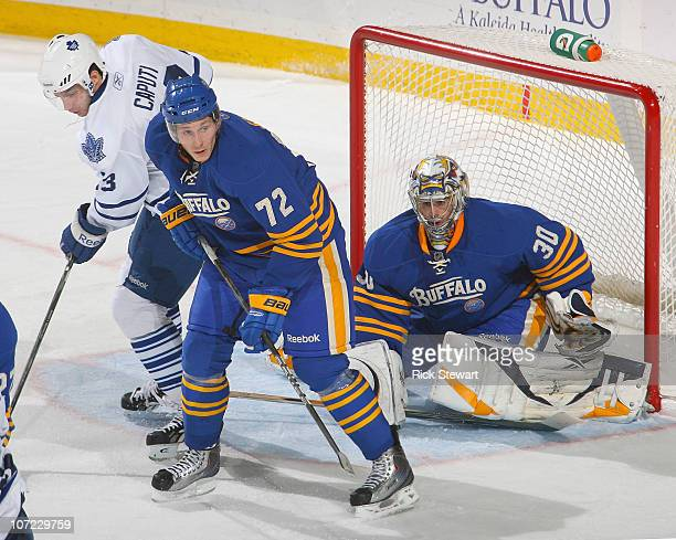 Luke Adam and Ryan Miller of the Buffalo Sabres defend against Luca Caputi of the Toronto Maple Leafs at HSBC Arena on November 26 2010 in Buffalo...