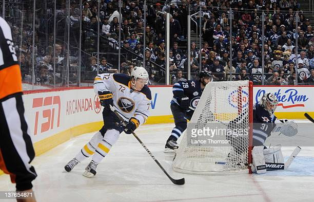 Luke Adam of the Buffalo Sabres carries the puck around the net as goaltender Ondrej Pavelec of the Winnipeg Jets keeps an eye on the play during...