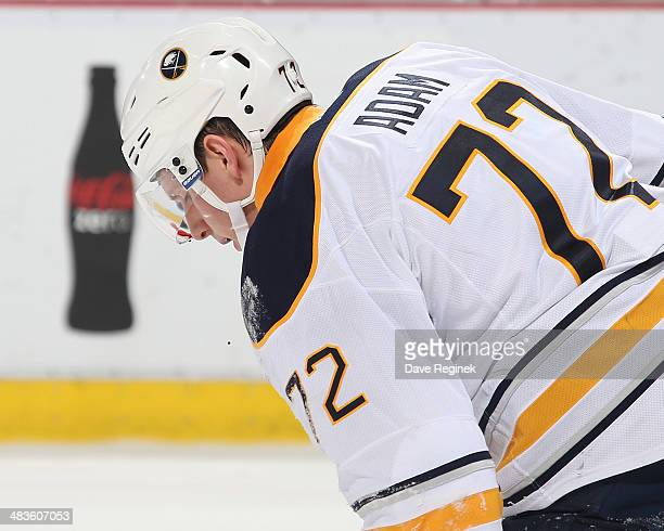 Luke Adam of the Buffalo Sabres skates off the ice after getting hit in the mouth with a puck during an NHL game against the Detroit Red Wings on...