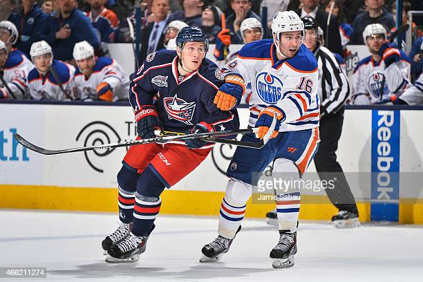 Luke Adam of the Columbus Blue Jackets skates and Teddy Purcell of the Edmonton Oilers battle for position on March 13 2015 at Nationwide Arena in...