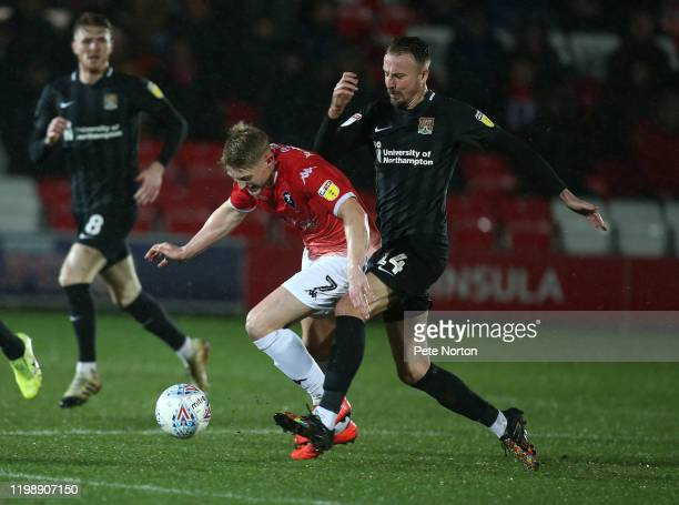 Luke Armstrong of Salford City goes to ground under the challenge of Chris Lines of Northampton Town during the Sky Bet League Two match between...