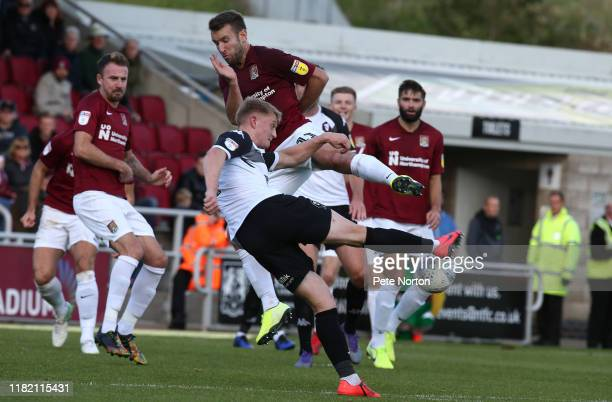 Luke Armstrong of Salford City has a shot at goal under pressure from Andy Williams of Northampton Town during the Sky Bet League Two match between...