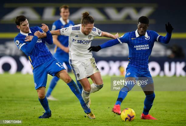 Luke Ayling of Leeds United is challenged by Pascal Gross and Yves Bissouma of Brighton & Hove Albion during the Premier League match between Leeds...