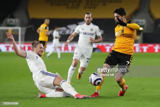 Luke Ayling of Leeds United tackles Pedro Neto of Wolverhampton Wanderers during the Premier League match between Wolverhampton Wanderers and Leeds...
