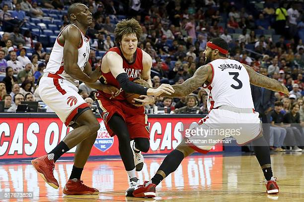 Luke Babbitt of the New Orleans Pelicans drives between Bismack Biyombo of the Toronto Raptors and James Johnson of the Toronto Raptors during the...