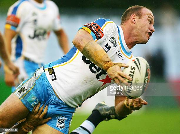 Luke Bailey of the Titans gets a pass away as a Sharks player has a hand on his crotch during the round 12 NRL match between the Cronulla Sharks and...