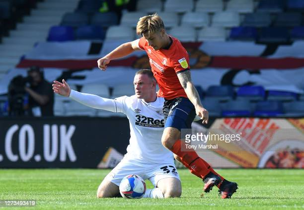 Luke Berry of Luton Town tackles Wayne Rooney of Derby County during the Sky Bet Championship match between Luton Town and Derby County at Kenilworth...