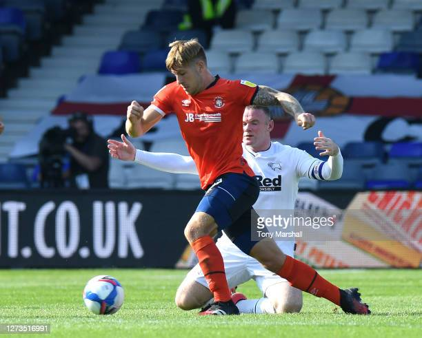 Luke Berry of Luton Town wins the ball from Wayne Rooney of Derby County during the Sky Bet Championship match between Luton Town and Derby County at...