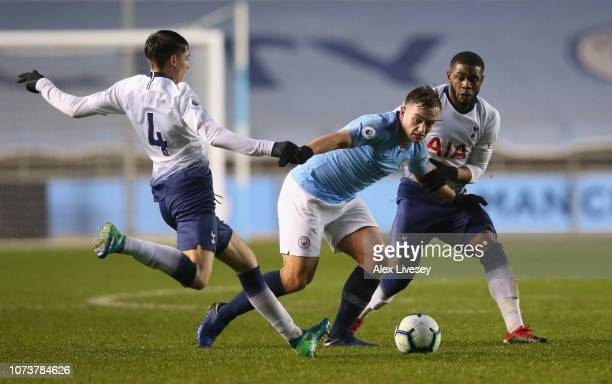 Luke Bolton of Manchester City is tackled by Jamie Bowden and Japhet Tanganga of Tottenham Hotspur during the Premier League 2 match between...