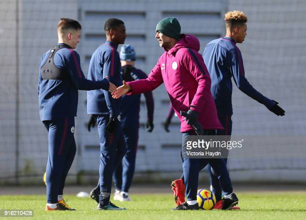 Luke Bolton Sadou Diallo and Felix Nmecha shake hands with Pep Guardiola during training at Manchester City Football Academy on February 9 2018 in...