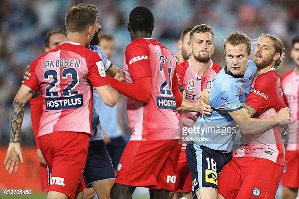 Luke Brattan of Melbourne City holds back Matt Simon of Sydney FC as he exchanges heated words with Michael Jakobsen of Melbourne City during the...