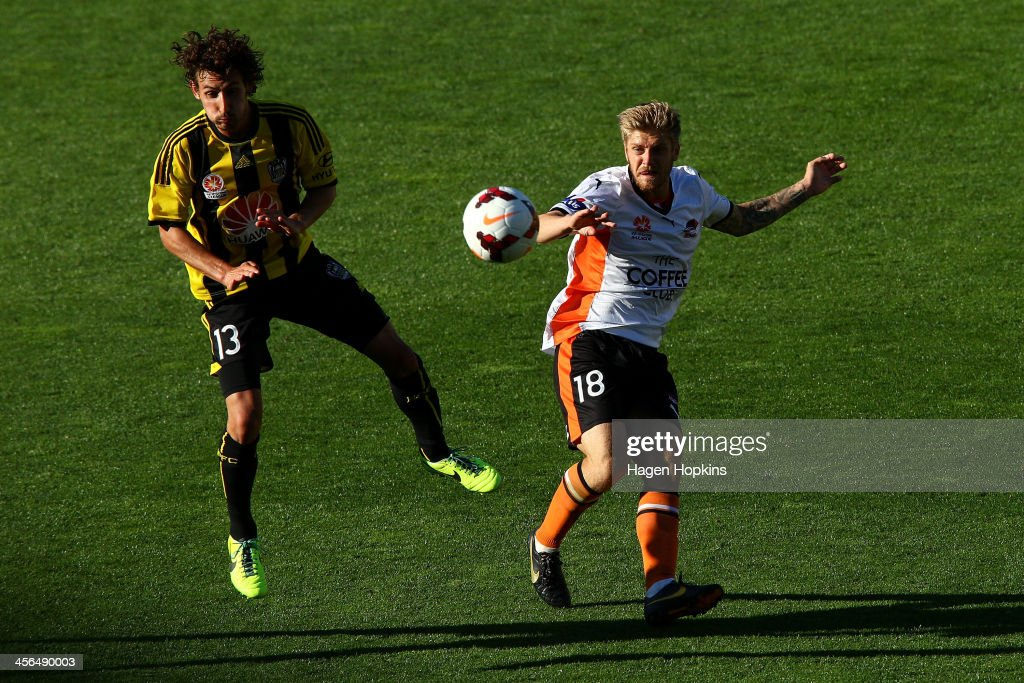 Luke Brattan of the Roar passes through the defence of Albert Riera of the Phoenix during the round 10 A-League match between the Wellington Phoenix and Brisbane Roar at Westpac Stadium on December 14, 2013 in Wellington, New Zealand.