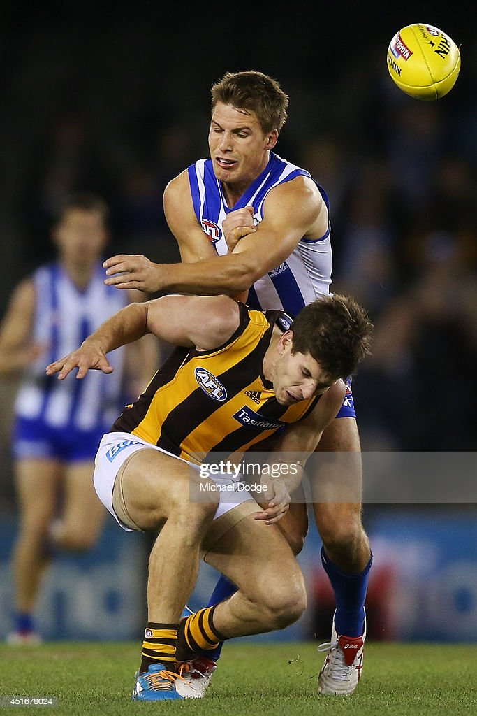 Luke Breust of the Hawks is tackled by Andrew Swallow of the Kangaroos during the round 16 AFL match between North Melbourne Kangaroos and the Hawthorn Hawks at Etihad Stadium on July 4, 2014 in Melbourne, Australia.