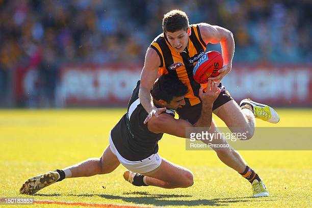 Luke Breust of the Hawks is tackled by Domenic Cassisi of the Power during the round 20 AFL match between the Hawthorn Hawks and the Port Adelaide...