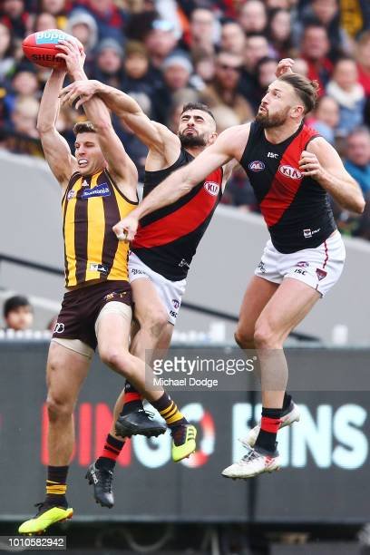 Luke Breust of the Hawks marks the ball against Adam Saad and Cale Hooker of the Bombers during the round 20 AFL match between the Hawthorn Hawks and...
