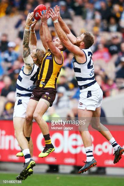 Luke Breust of the Hawks marks the ball against Tom Stewart of the Cats and Lachie Henderson of the Cats during the round 21 AFL match between the...
