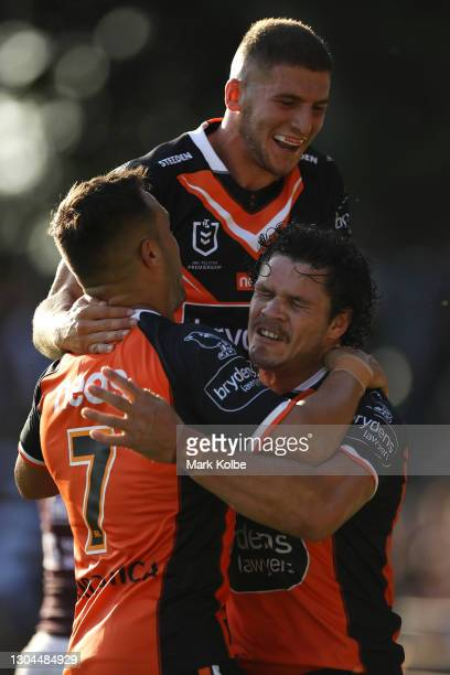 Luke Brooks, Adam Doueihi and James Roberts of the Tigers celebrates James Roberts scoring a try during the NRL Trial Match between the Wests Tigers...