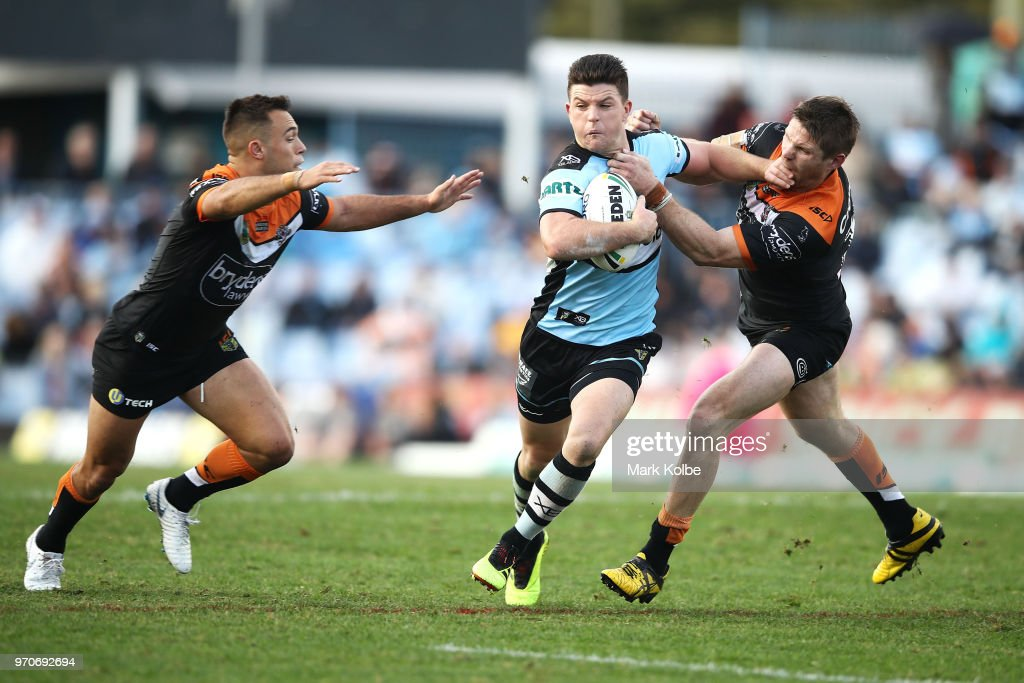 Luke Brooks (L) and Chris Lawrence (R) of the Tigers tackle Chad Townsend of the Sharks during the round 14 NRL match between the Cronulla Sharks and the Wests Tigers at Southern Cross Group Stadium on June 10, 2018 in Sydney, Australia.