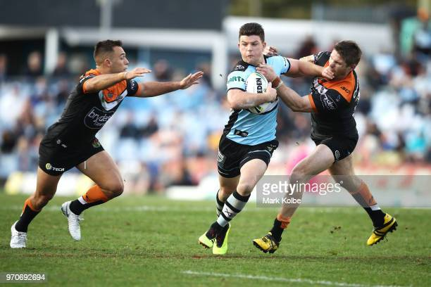 Luke Brooks and Chris Lawrence of the Tigers tackle Chad Townsend of the Sharks during the round 14 NRL match between the Cronulla Sharks and the...