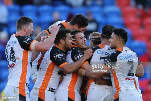 Luke Brooks of the Tigers celebrates his try with his team during the round 17 NRL match between the Newcastle Knights and the Wests TIgers at...