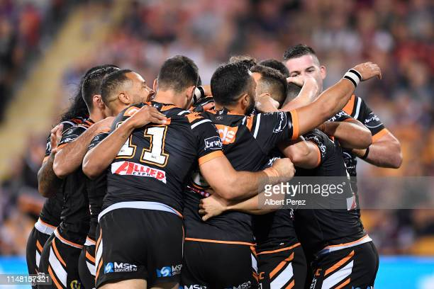 Luke Brooks of the Tigers celebrates with team mates after scoring his team's second try during the round nine NRL match between the Wests Tigers and...